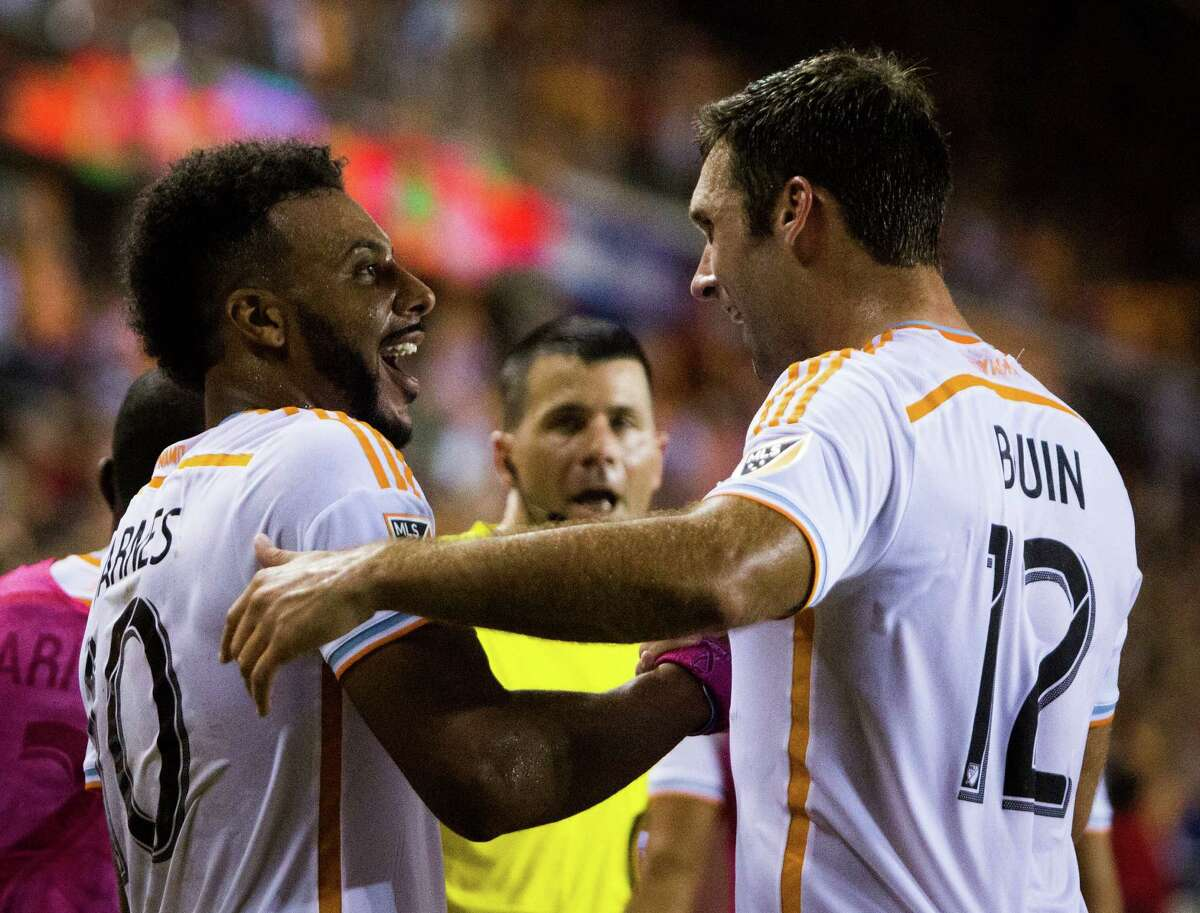 Houston Dynamo forward Will Bruin (12), right, congratulates Houston Dynamo forward Giles Barnes (10) after Barnes scored a goal during the second half of the game against the Portland Timbers, Saturday, May 16, 2015, in Houston.