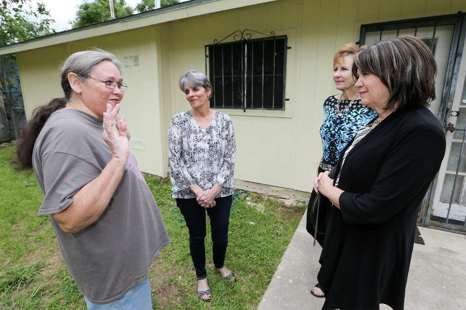 Donna Harrison (from right), President of Impact San Antonio, Jeanne Albrect, board member of Impact San Antonio and Dee Dee Sedgwick, Executive Director of Blueprint Ministries visit with Ramona Alcarez outside her home on Tuesday, April 28, 2015. Blueprint Ministries is in the process of making to repairs to the Alcarez residence with funds provided by Impact San Antonio. MARVIN PFEIFFER/ mpfeiffer@express-news.net Photo: Marvin Pfeiffer /San Antonio Express-News / Express-News 2015