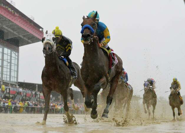 American Pharaoh, center, with jockey Victor Espinoza flies across a very muddy track the first time by the clubhouse on the to the win in the 140th running of the Preakness Stakes held at Pimlico Race Course Saturday evening May 16, 2015 in Baltimore, MD  (Skip Dickstein/Times Union) Photo: SKIP DICKSTEIN, ALBANY TIMES UNION