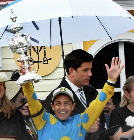 Jockey Victor Espinoza holds the winner's trophy aloft after American Pharaoh won the 140th running of the Preakness Stakes held at Pimlico Race Course Saturday evening May 16, 2015 in Baltimore, MD  (Skip Dickstein/Times Union) Photo: SKIP DICKSTEIN, ALBANY TIMES UNION