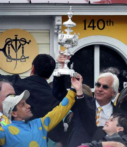 Jockey Victor Espinoza, left and trainer Bob Baffert hold the winner's trophy aloft after American Pharaoh won the 140th running of the Preakness Stakes held at Pimlico Race Course Saturday evening May 16, 2015 in Baltimore, MD  (Skip Dickstein/Times Union) Photo: SKIP DICKSTEIN, ALBANY TIMES UNION