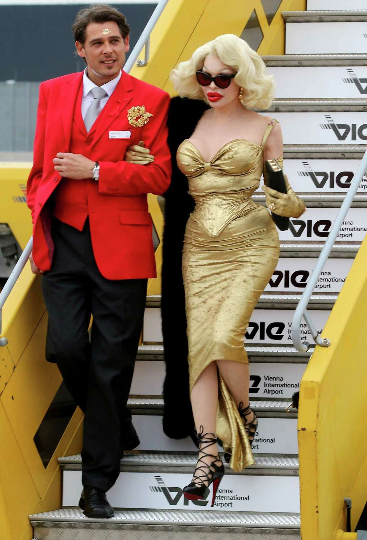 US transgender star Amanda Lepore, right, arrives for the largest annual AIDS charity gala in Europe known as the Life Ball, at the Vienna International airport near Schwechat, Austria, Friday, May 15, 2015.
