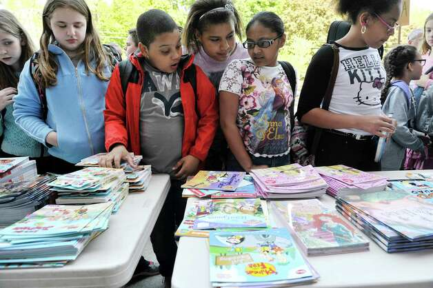 Children look over books before picking two out during a book giveaway at  Central Park International Magnet School on Thursday, May 14, 2015, in Schenectady, N.Y.  The book program is a partnership between First Book, the American Federation of Teachers (AFT), and New York State United Teachers (NYSUT) and Schenectady Federation of Teachers.  Each child was allowed to pick out two books during the event.  500,000 free books are being given out to children in the area through the program.  (Paul Buckowski / Times Union) Photo: PAUL BUCKOWSKI, Albany Times Union / 00031825A