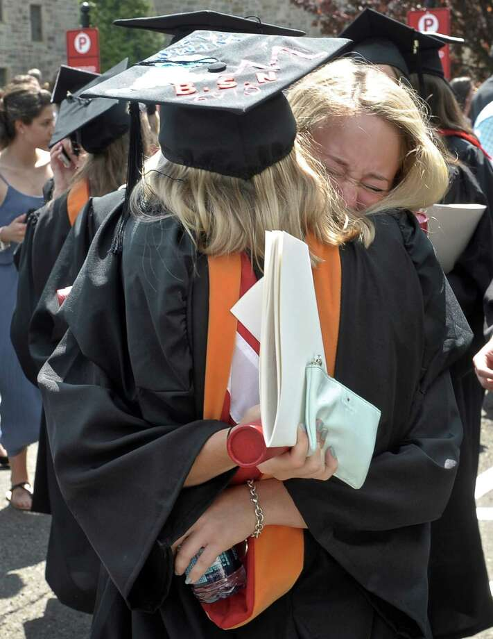 Meghan Weiser, of Yardley PA, right, hugs fellow graduate Alyssa Acompora , of West Islip, NY, after the 2015 Fairfield University  Commencement held on the Bellarmine Terrace of Fairfield University, Sunday morning, May 17, 2015, in Fairfield, Conn. Weiser and Acompora earned their degrees from the School of Nursing. Photo: H John Voorhees III / The News-Times