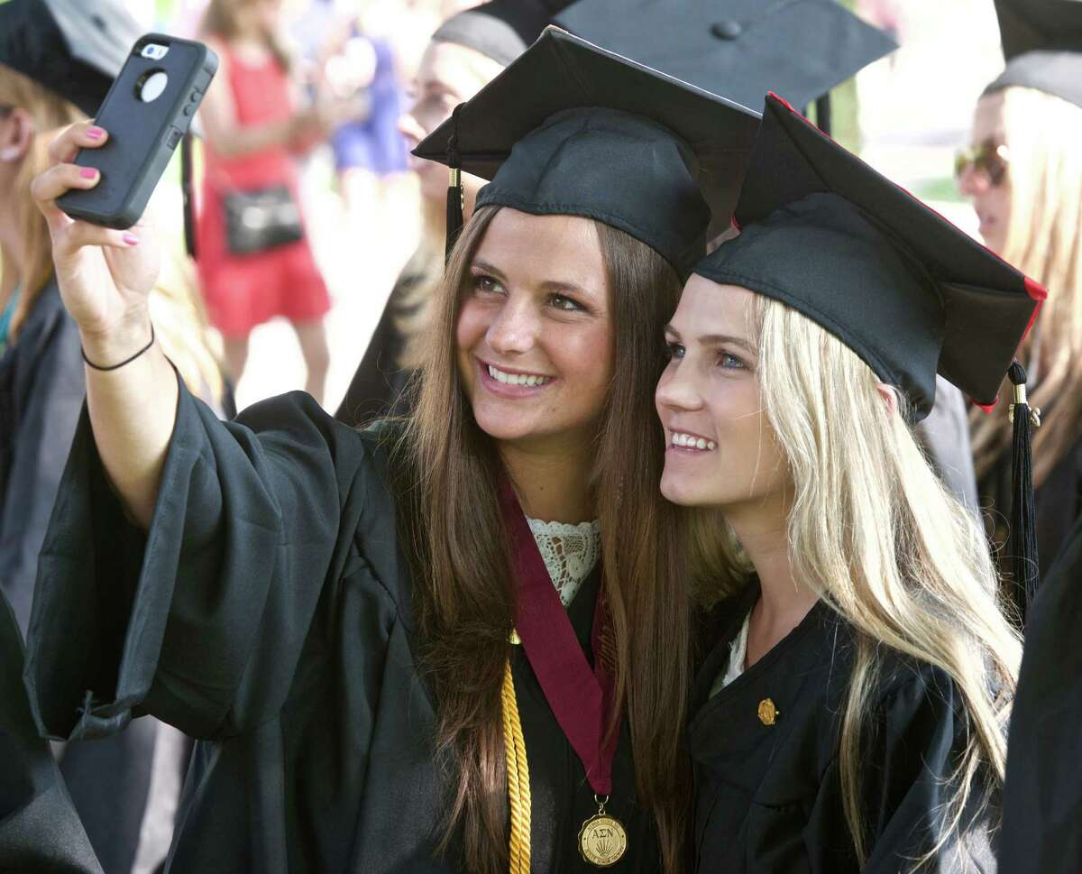 Kayla Arnold, from Long Island, New York, left, and Meghan Bonner, from Pennsylvania, take a photo while waiting in line for the Fairfield University 2015 Commencement Undergraduate Exercises to begin. The event was held on the Bellarmine Terrace of Fairfield University, Sunday morning, May 17, 2015, in Fairfield, Conn. Arnold and Bonner earned their degrees from the School of Nursing.