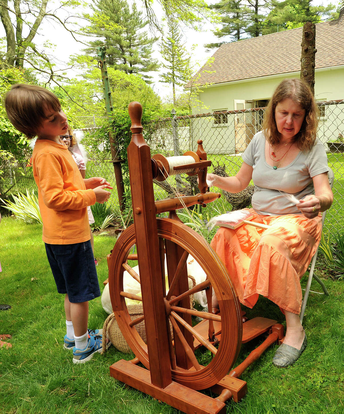 Ace Grossman watches Gale Organist spin wool into yarn during the Greenwich Historical Society's Spring Fling at French Farm in Greenwich, Conn., on Sunday, May 17, 2015.