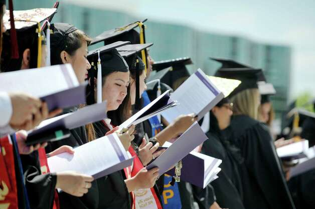 Graduates stand to sing the schools fight song during the University at Albany commencement on Sunday, May 17, 2015, in Albany, N.Y.    (Paul Buckowski / Times Union) Photo: PAUL BUCKOWSKI / 00031518A