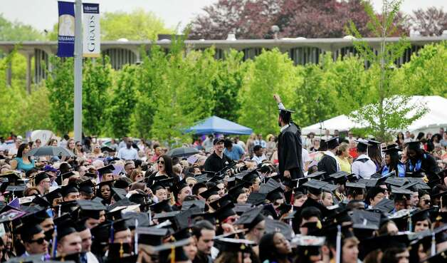 A graduate stands on his chair to wav to family and friends  during the University at Albany commencement on Sunday, May 17, 2015, in Albany, N.Y.    (Paul Buckowski / Times Union) Photo: PAUL BUCKOWSKI / 00031518A