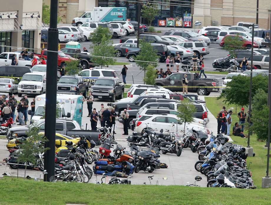 "Law enforcement officers investigate a shooting in the parking lot of the Twin Peaks Restaurant Sunday, May 17, 2015, in Waco, Texas. Waco police Sgt. W. Patrick Swanton told KWTX-TV there were ""multiple victims"" after gunfire erupted between rival biker gangs at the restaurant. AP story: Police: 9 dead from Texas shootout among rival biker gangs Photo: Rod Aydelotte, AP / Waco Tribune Herald"