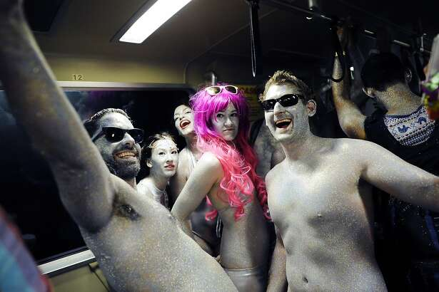 Marko Markovic, left, Zillah Smith, and William Grossman ride the BART with other members of the Silver Glitter Group as they head towards the 103rd Bay to Breakers event in San Francisco, CA Sunday, May 17, 2015