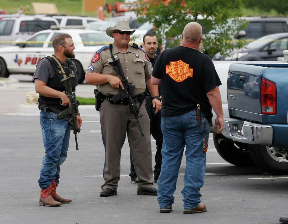 "Law enforcement officers talk to a man near the parking lot of a Twin Peaks Restaurant Sunday, May 17, 2015, in Waco, Texas, after a shooting involving rival biker gangs. Waco police Sgt. W. Patrick Swanton told KWTX-TV there were ""multiple victims"" after gunfire erupted between the gang members. (Rod Aydelotte/Waco Tribune Herald via AP) Photo: Rod Aydelotte / Associated Press / Waco Tribune Herald"