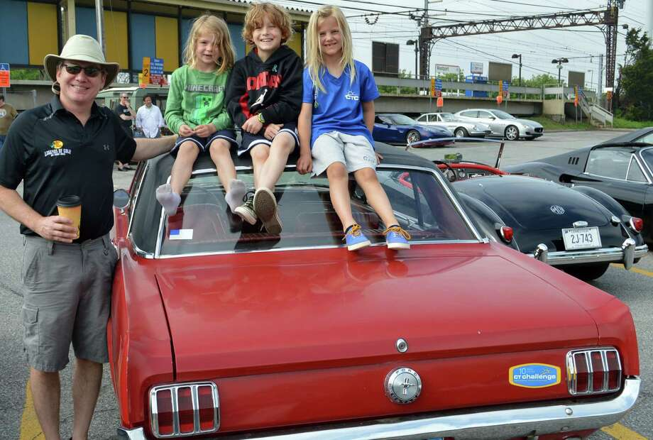Jeff Manchester of Westport lets a trio of youngsters -- his kids Ella, 6, and Logan, 9, and friend Sarah Von Dohlen, 6 -- relax atop the 1966 Mustang his mother bought new in Texas, which he brought to Sunday's Concours d'Caffeine car show. Photo: Jarret Liotta / Westport News