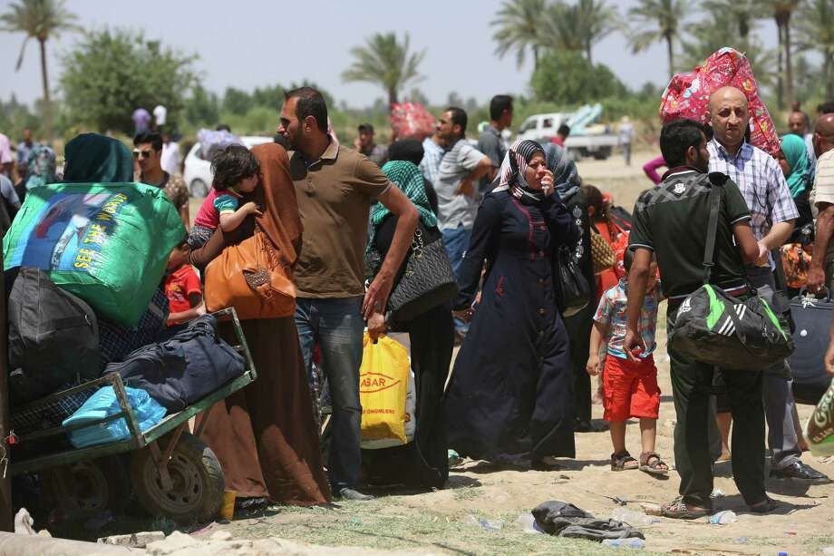 Iraqis fleeing from their hometown of Ramadi rest about halfway on their journey to Baghdad. The Islamic State group seized control of Ramadi on Sunday, sending Iraqi forces racing out of the city in a major loss. Photo: Hadi Mizban, STF / AP