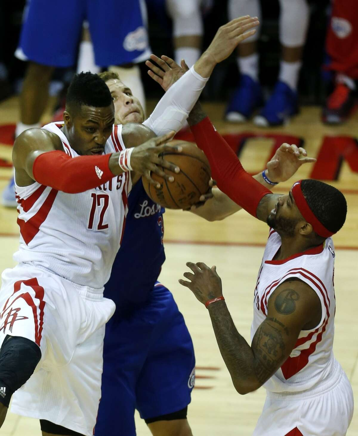 Houston Rockets center Dwight Howard (12) pulls down a rebound against Los Angeles Clippers forward Blake Griffin (32), with Rockets forward Josh Smith (5) in on the play during the second quarter of Game 7 of the NBA Western Conference semifinals at Toyota Center on Sunday, May 17, 2015, in Houston. ( Karen Warren / Houston Chronicle )