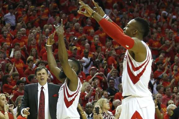 Houston Rockets guard James Harden (13), left, and  Rockets center Dwight Howard (12) points to the sky as they come off the court at the end of Game 7 of the NBA Western Conference semifinals win over the Los Angeles Clippers at the Toyota Center Sunday, May 17, 2015, in Houston.  The Rockets beat the Clippers 113-100, to win the best-of-seven series 4-3. ( James Nielsen / Houston Chronicle )