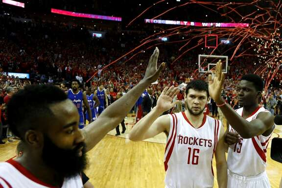 Houston Rockets guard James Harden, left, high fives forward Kostas Papanikolaou (16) and center Clint Capela (15) as he comes off the court at the end of Game 7 of the NBA Western Conference semifinals win over the Los Angeles Clippers at the Toyota Center Sunday, May 17, 2015, in Houston.  The Rockets beat the Clippers 113-100, to win the best-of-seven series 4-3. ( James Nielsen / Houston Chronicle )
