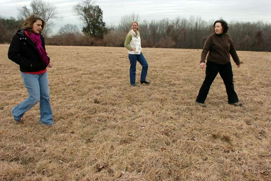 Sharna Kozak, Allison Menedez and Teresa Gallagher walk through a field on the Klapik Farm open space, in Shelton, Conn. March 11th, 2010. They are members of the Shelton Community Garden Committee, who hope to see a community garden established on the town owned property. Neigbors of the property are opposed. Photo: Ned Gerard / Connecticut Post