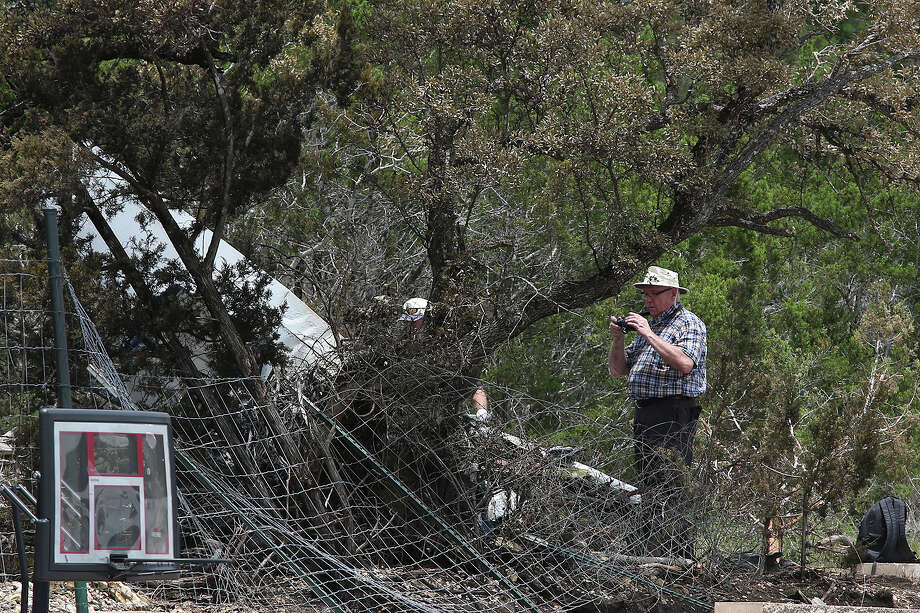 National Transportation Safety Board and Federal Aviation Administration investigators look for clues at the scene of a plane crash in Spring Branch, Sunday, May 17, 2015. Emergency personnel responded to the scene on Saturday and found that Michael Scott Galloway, 38, his wife, Louise Galloway, 32, and their two children, Clayton, 10 and Cheyenne Elizabeth, 8, died in the fiery crash. The single-engine Piper PA-24 had just departed Kestrel Air Park near the crash site. Photo: JERRY LARA, Staff / San Antonio Express-News / © 2015 San Antonio Express-News