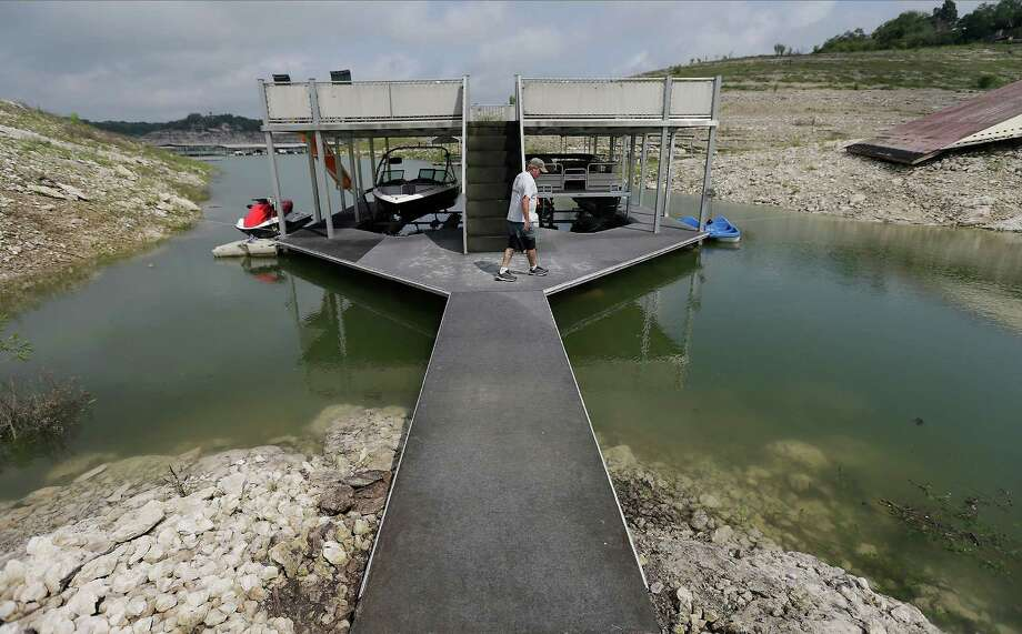 Medina Lake advocate and businessman Mike Crandall walks onto a boat dock at Medina Lake after the past week's weather event dropped a significant amount of rain into the area on Saturday, May 16, 2015. Though the rain contributed to a much needed rise in the amount of water in the lake, the once popular water recreation spot is still at drought-stricken levels. Home owners and business people like Crandall who owns Wally's Water Sports since 1990 are happy about the rain fall but are still hoping for more rain to help bring the lake back to pre-drought conditions. (Kin Man Hui/San Antonio Express-News) Photo: Kin Man Hui, Staff / San Antonio Express-News / ©2015 San Antonio Express-News
