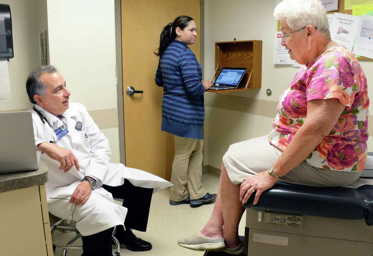 Dr. Paul Barbarotto, left, and medical scribe Saima Akhter with patient Leslie Palmer, right, during an exam at Capital Region Family Health Wednesday May 6, 2015 in Rensselaer, NY. (John Carl D'Annibale / Times Union)