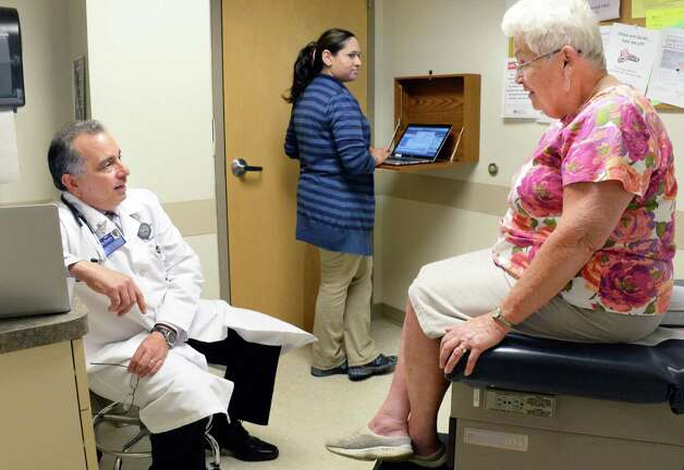 Dr. Paul Barbarotto, left, and medical scribe Saima Akhter with patient Leslie Palmer, right, during an exam at Capital Region Family Health Wednesday May 6, 2015 in Rensselaer, NY.  (John Carl D'Annibale / Times Union) Photo: John Carl D'Annibale / 0507_medscribes