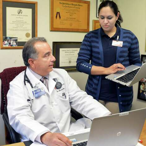 Dr. Paul Barbarotto, left, and medical scribe Saima Akhter review a patient exam at Capital Region Family Health Wednesday May 6, 2015 in Rensselaer, NY.  (John Carl D'Annibale / Times Union) Photo: John Carl D'Annibale / 0507_medscribes