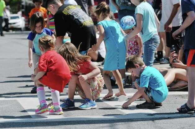 Children scurry to collect pieces of candy at the Altamont Memorial Day Parade on Sunday, May 17, 2015, in Altamont, N.Y.    (Paul Buckowski / Times Union) Photo: PAUL BUCKOWSKI / 00031853A
