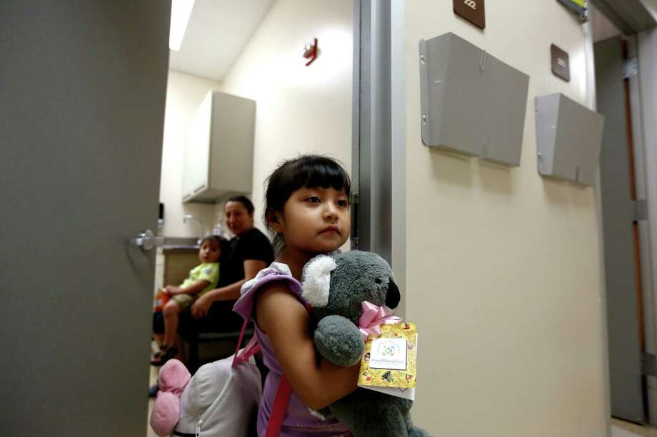 Four-year-old Marta Villegas, with her mother and younger brother, visits a doctor  at the Good Neighbor Healthcare Center on Friday and she received a stuffed koala from the Cuddly Neighbor Program to help children relax during office visits. Photo: Gary Coronado, Staff / © 2015 Houston Chronicle