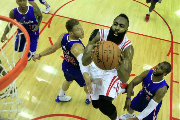 Houston Rockets guard James Harden (13) drives in for a layup past Los Angeles Clippers forward Blake Griffin (32) and Chris Paul (3) during the first half of Game 7 of the NBA Western Conference semifinals at the Toyota Center Sunday, May 17, 2015, in Houston. The Rockets beat the Clippers 113-100, to win the best-of-seven series 4-3 ( James Nielsen / Houston Chronicle )