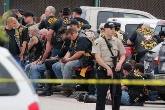 A McLennan County deputy stands guard near a group of bikers outside the Twin Peaks Restaurant.
