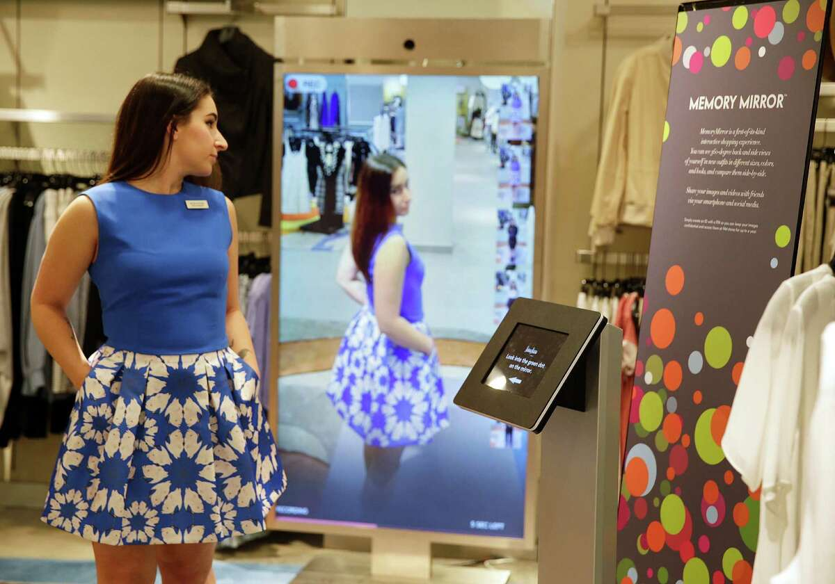 Sales manager Alysa Stefani demonstrates the MemoryMirror at a Neiman Marcus store in San Francisco. The mirror is outfitted with sensors, setting off motion-triggered changes of clothing. The mirror also doubles as a video camera,