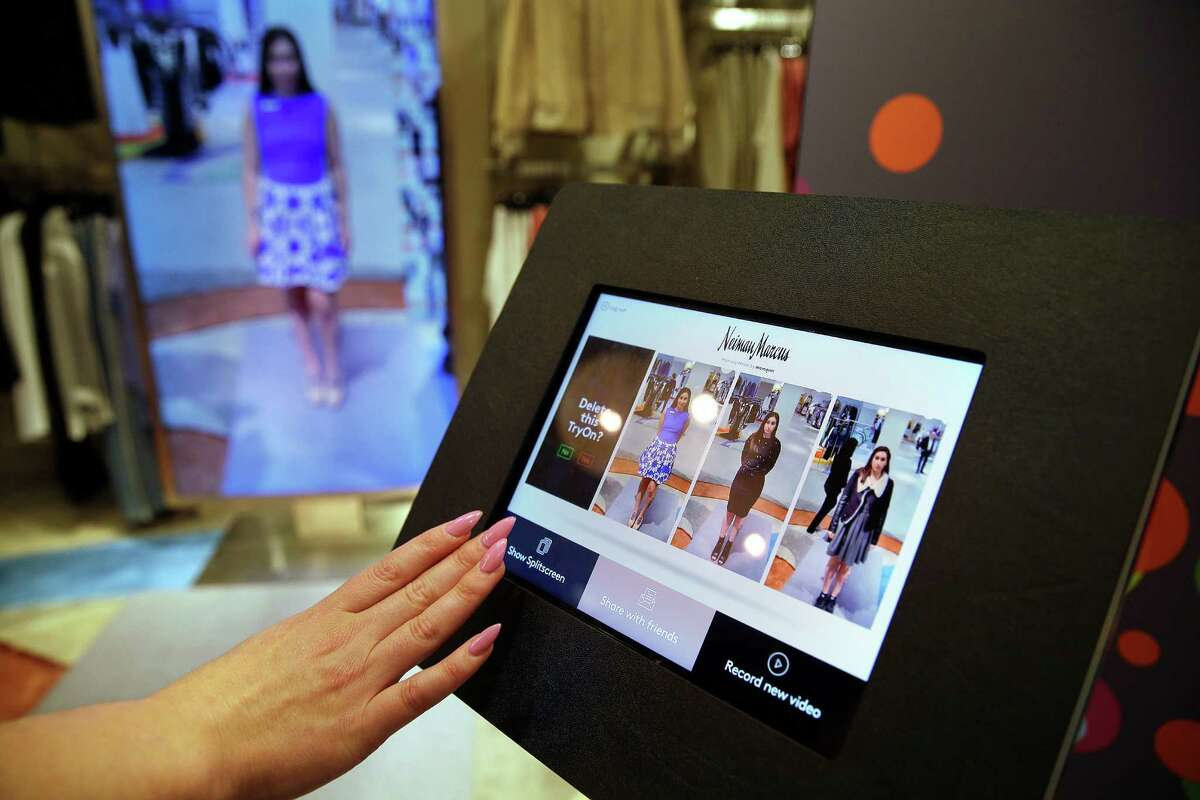 Sales manager Alysa Stefani uses a touch-screen display to make selections while demonstrating the MemoryMirror.