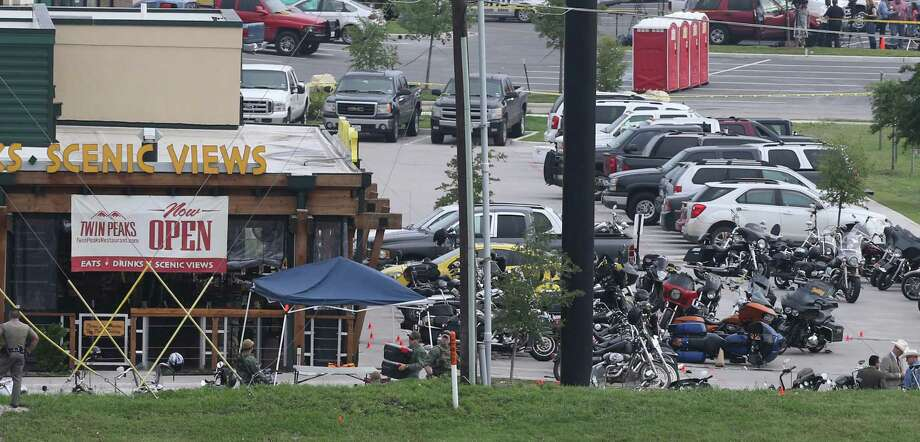 Law enforcement continue to investigate the motorcycle gang related shooting at the Twin Peaks restaurant, Monday, May 18, 2015, in Waco, Texas, where 9 were killed Sunday and over a dozen injured. Waco police on Monday announced the Texas Alcoholic Beverage Commission closed Twin Peaks for a week amid safety concerns.  (AP Photo, Jerry Larson) Photo: Jerry Larson, Associated Press / FR91203 AP