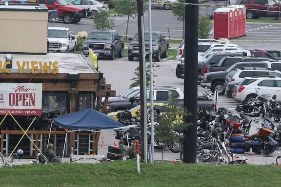 Law enforcement continue to investigate the motorcycle gang related shooting at the Twin Peaks restaurant, Monday, May 18, 2015, in Waco, Texas, where 9 were killed Sunday and over a dozen injured. Waco police on Monday announced the Texas Alcoholic Beverage Commission closed Twin Peaks for a week amid safety concerns.  (AP Photo, Jerry Larson)