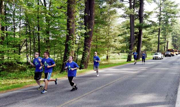 Saratoga Springs Police officer Eric Warfield carries the torch down the Avenue of the Pines during the Special Olympics Torch Run Monday morning May 18, 2015 in Saratoga Springs, N.Y.  Torches carried by law enforcement members from throughout the state will end up at the opening ceremony's of this years State Special Olympics on June 6th at the University of Brockport.    (Skip Dickstein/Times Union) Photo: SKIP DICKSTEIN / 00031855A