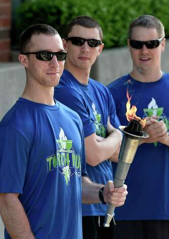 Saratoga Springs Police officer Eric Warfield, left  carries the torch during the kick off of the Special Olympics Torch Run Monday morning May 18, 2015 in Saratoga Springs, N.Y.  Torches carried by law enforcement members from throughout the state will end up at the opening ceremony's of this years State Special Olympics on June 6th at the University of Brockport.    (Skip Dickstein/Times Union) Photo: SKIP DICKSTEIN / 00031855A
