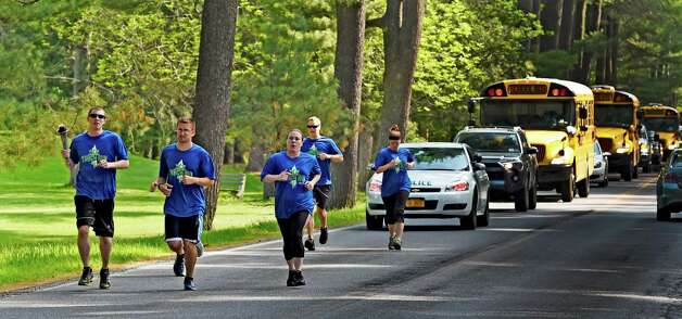 Saratoga Springs Police officer Eric Warfield carries the torch during the kick off of the Special Olympics Torch Run Monday morning May 18, 2015 in Saratoga Springs, N.Y.  Torches carried by law enforcement members from throughout the state will end up at the opening ceremony's of this years State Special Olympics on June 6th at the University of Brockport.    (Skip Dickstein/Times Union) Photo: SKIP DICKSTEIN / 00031855A