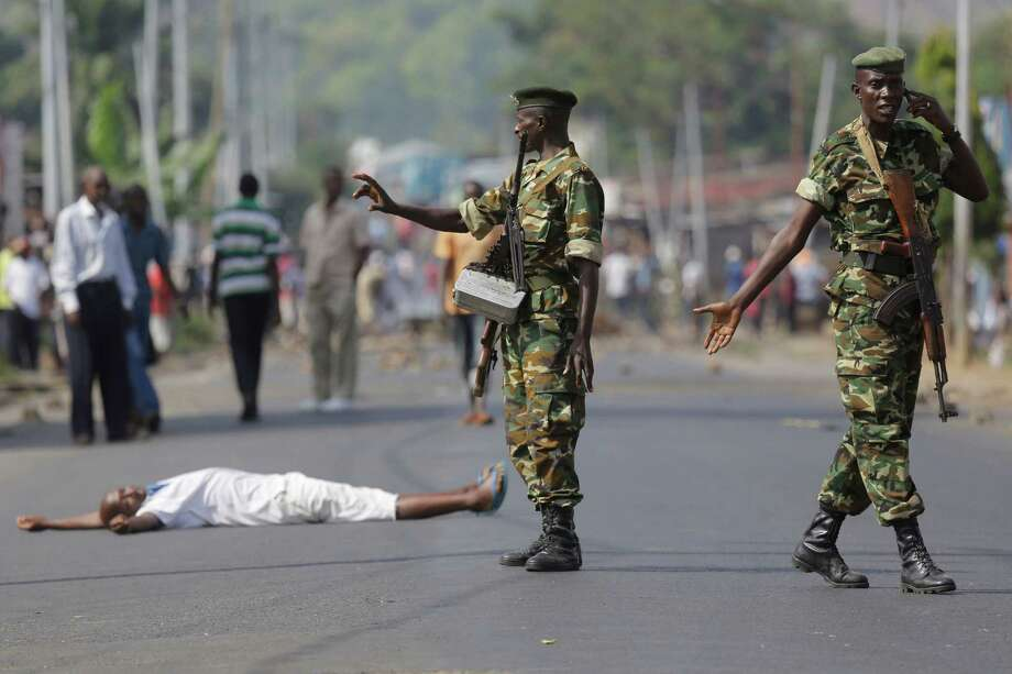 A demon strator lays down on a road to protest soldiers who fired shots to disperse crowds in the Musaga district of Bujum bura. Photo: Jerome Delay / Associated Press / AP