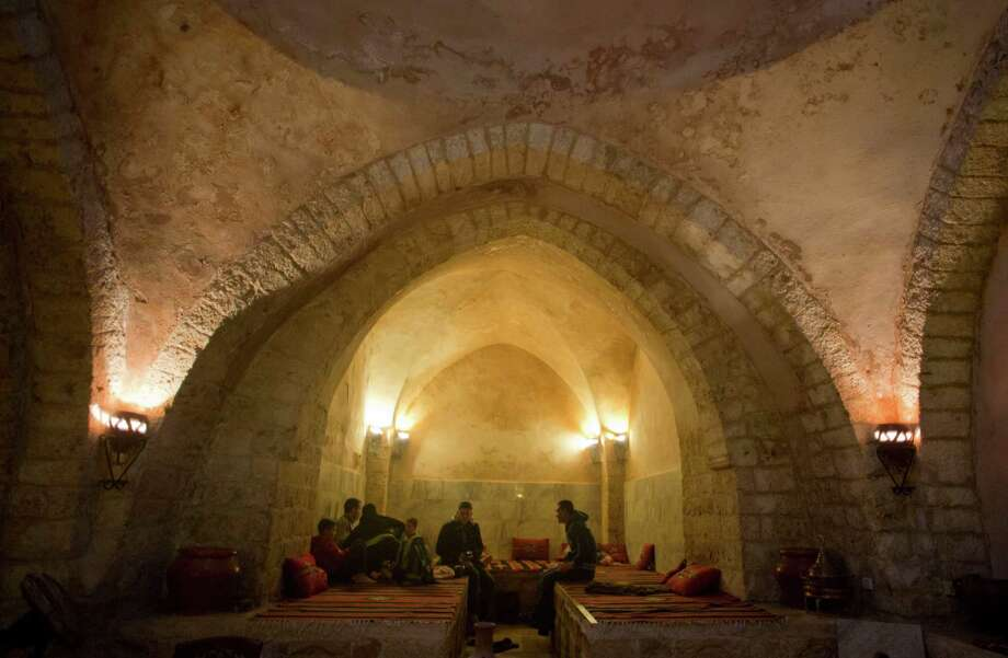 Palestinian men relax before taking the steam at Hamam al-Sumara, a centuries-old bathhouse in Gaza City. The bath dates back 1,000 years, and is the only one left in a city that once boasted a half dozen. Photo: Khalil Hamra / Associated Press / AP
