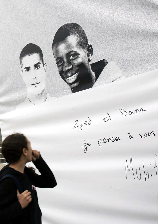 "FILE - In this Oct. 20, 2006 file photo, a resident walks past photos of Zyed Benna, left, and Bouna Traore who died after being electrocuted in a power substation while hiding from police on Oct. 27, 2005 in Clichy-Sous-Bois, outside Paris.  A French court has acquitted Monday, May 18, 2015 two police officers who were accused of contributing to the deaths of two teenagers in a blighted Paris suburb a decade ago. Poster reads: ""Zyed and Bouna, I will not forget you"". Photo: Christophe Ena / Associated Press / AP"