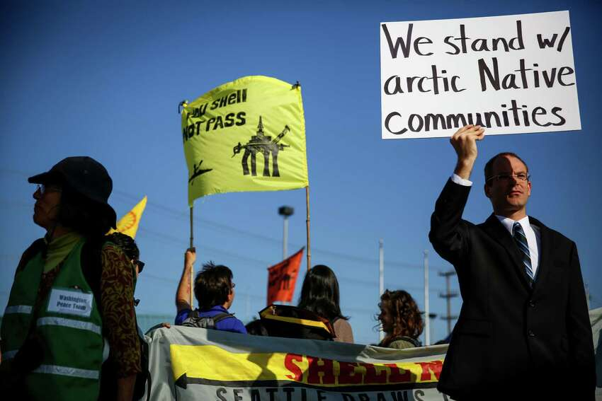 Protesters, including University of Washington student David Herman, right, hold up signs during a protest against Arctic oil drilling and the mooring of Shell Oil's Polar Pioneer drilling rig in Seattle. Protesters blocked entrances to the port during the protest. Photographed on Monday May 18, 2015.