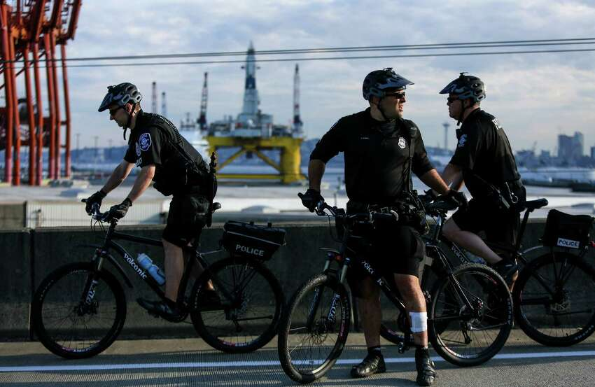 Seattle Police officers ride in front of officers during a protest against Arctic oil drilling and the mooring of Shell Oil's Polar Pioneer drilling rig in Seattle. Protesters blocked entrances to the port during the protest. Photographed on Monday May 18, 2015.