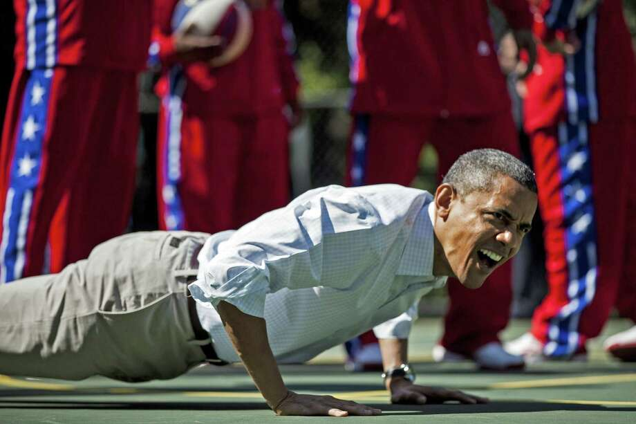 US President Barack Obama does pushups during backetball shooting drills during the annual Easter Egg Roll on the South Lawn of the White House April 9, 2012 in Washington, DC.  The First Family participated in the yearly event where the South Lawn is opened up to guests to participate in various egg rolls and other activities.  AFP PHOTO/Brendan SMIALOWSKI        (Photo credit should read BRENDAN SMIALOWSKI/AFP/Getty Images) Photo: BRENDAN SMIALOWSKI, Staff / AFP/Getty Images / AFP