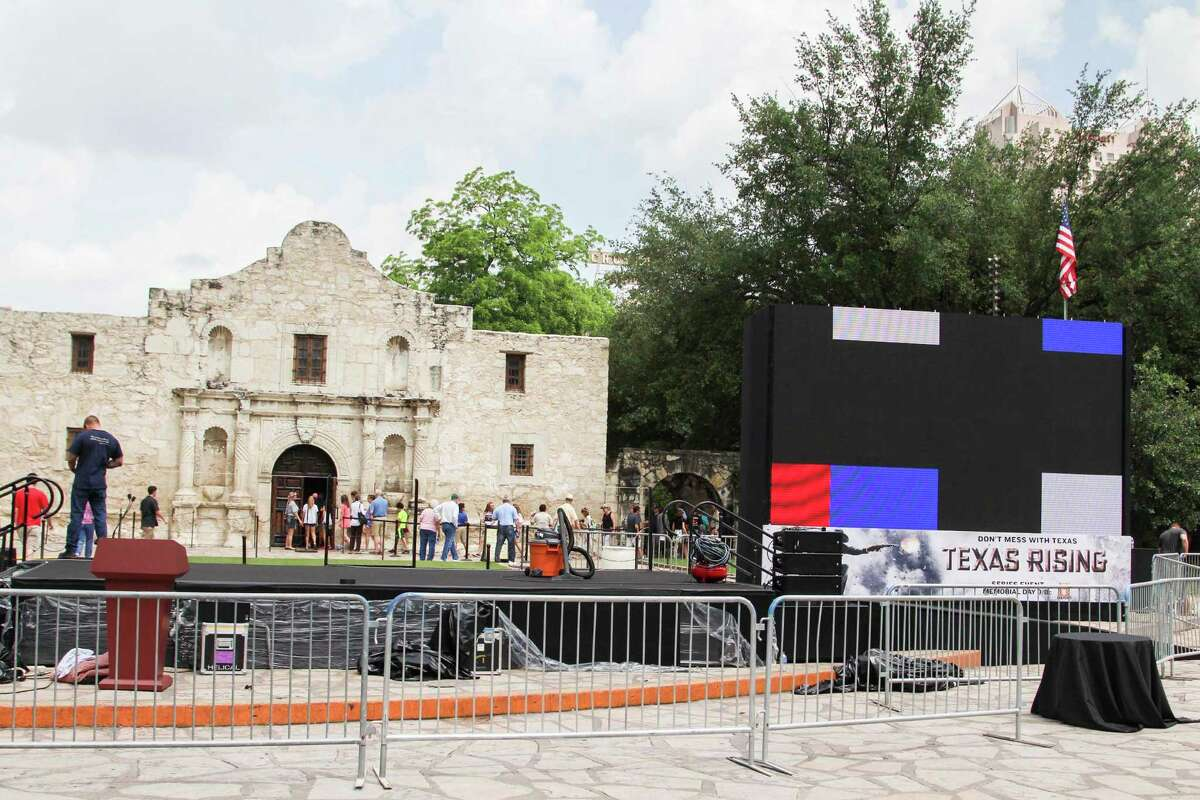 Crew members work to setup a red carpet gala into the Alamo Monday for a special preview of the upcoming