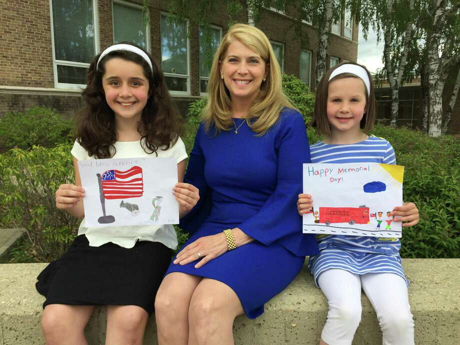 Winners of the third annual Memorial Day Parade Childrenís Drawing Contest Julie McTigue, left, and Caroline Ward, right, showcase their artwork for First Selectman Jayme Stevenson. Photo: Contributed Photo / Darien News