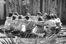 View of participants as they sit in a circle, arms over one another's shoulders, during a nude encounter group therapy session at the Esalen Institute, Big Sur, California, Jan. 1, 1968. The Esalen Institute was a focal point for the Human Potential Movement, and featured a number of different workshops for attendees. This one, run by psychiatrist Paul Bindrim, was a Marathon Workshop where participants spent an extended period of time (20 - 48 hours) nude together in an effort to locate their 'real selves.'