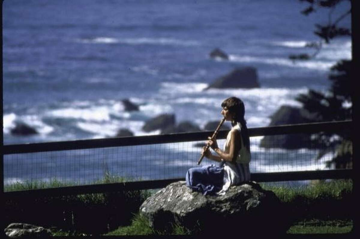 A woman sitting on a rock, playing a wooden flute, on the cliffs overlooking the Pacific Ocean at the Esalen Institute in Big Sur, Calif., onApril 1, 1987.