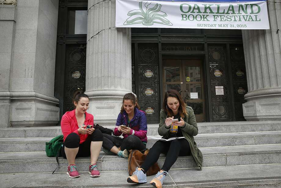 Oakland teachers Taylor Allbright, Rose Zapata, and Laura Hayes have their students do a downtown scavenger hunt as they monitor through their phones in front of city hall in Oakland, California, on Monday, May 18, 2015.  Behind is a banner over the front door of city hall announcing the Oakland Book Festival. Photo: Liz Hafalia, The Chronicle