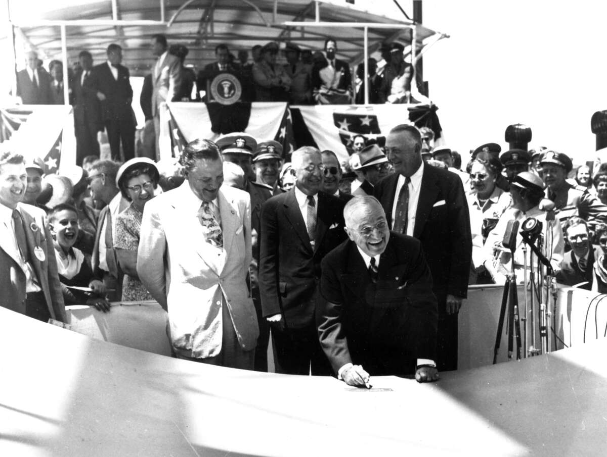 President Harry S. Truman smiles as he signs his initials to the keel plate of the USS Nautilus, the first atomic-powered submarine in history, during a ceremony at Groton, Conn., on June 14, 1952.