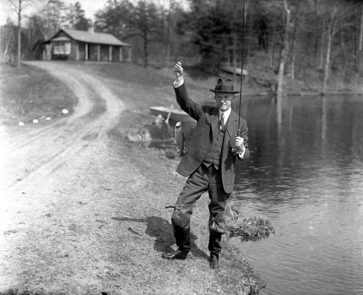 This is a 1932 photo of former U.S. President Calvin Coolidge posing with a trout he caught while fishing in Simsbury, Conn.
